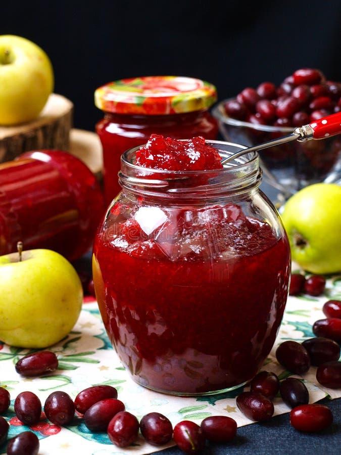 Domowej roboty dżem derenie i jabłka lokalizuje w słojach na stole, jeden słój jest otwarty zdjęcia royalty free