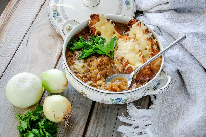 Domowej roboty Francuska Cebulkowa polewka z serem i grzanką na drewnianym tle zdjęcie royalty free