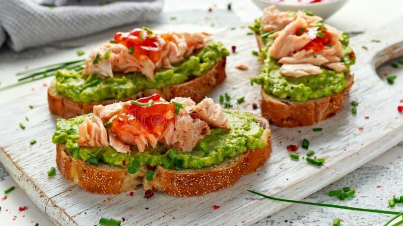 Domowej roboty grzanki kanapka z łososiem, Avocado i chili, przyskrzyniamy na wihte drewnianej desce zdrowa żywność obrazy stock