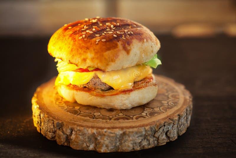 Domowej roboty hamburger na drewnianej desce Zmierzchu światło obraz royalty free