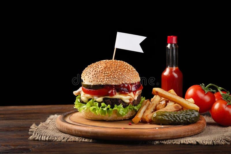Domowej roboty hamburger w g?r? z wo?owiny, pomidoru, sa?aty, sera i francuza d?oniak?w na tn?cej desce, Ma?a bia?a flaga wk?adaj fotografia royalty free