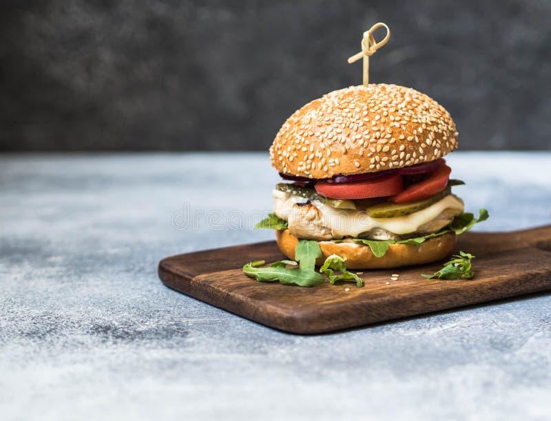 Domowej roboty hamburger z kurczakiem, arugula, serem i warzywami piec na grillu, obraz stock