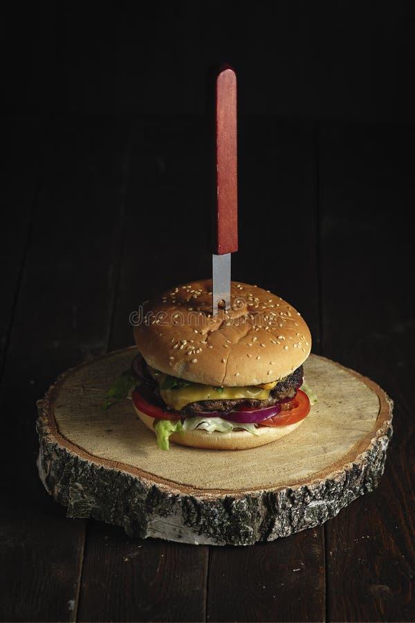 Domowej roboty hamburger z rozwidleniem na nieociosanym drewnianym tle zamkniętym w górę zdjęcie royalty free