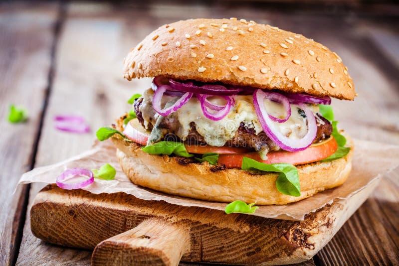Domowej roboty hamburger z wołowiny cutlet, jabłkiem, sałatą, cebulą i błękitnym serem, obraz royalty free