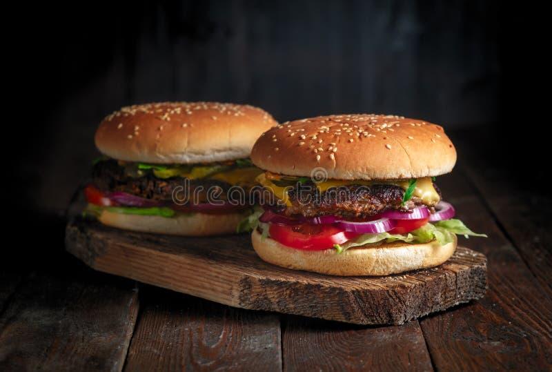 Domowej roboty hamburgery na nieociosanym drewnianym tle zamykają w górę zdjęcia stock
