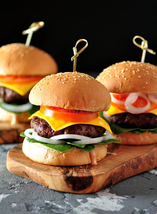 Domowej roboty hamburgery z kiszonym cebul, pomidoru i dziecka szpinakiem, obraz stock