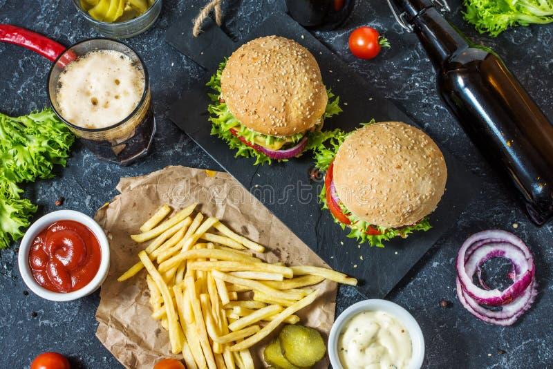 Domowej roboty hamburgery z wołowiną, smażący szkło zimny ciemny piwo na kamienia stole i grule i obrazy royalty free