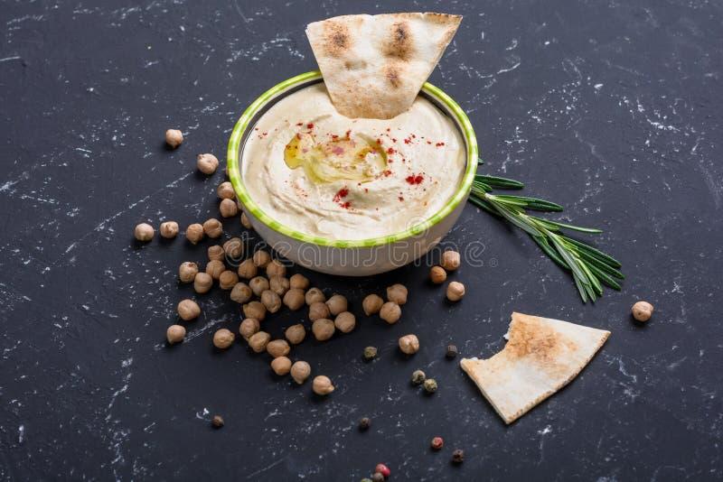 Domowej roboty hummus, chickpea fasole, rozmaryny z pita na czerń kamienia stole Bliskowschodnia tradycyjna i autentyczna arabska obraz royalty free