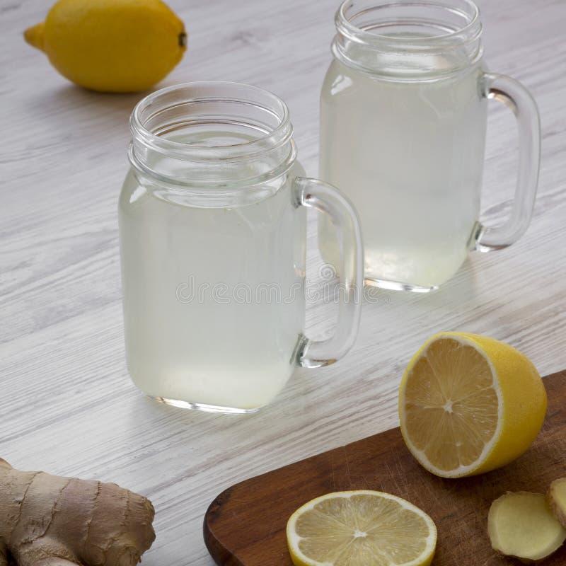 Domowej roboty imbirowa herbata z cytryną w szkle zgrzyta nad białym drewnianym tłem, niskiego kąta widok Zako?czenie fotografia stock