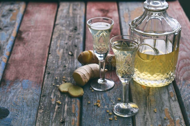 Domowej roboty imbirowy tincture lub ale na drewnianym tle Wieśniaka styl Pikantność żółty ajerkoniak w szkle Alkoholu napój zdjęcia stock
