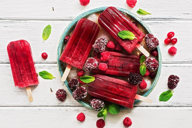 Domowej roboty jagodowi popsicles dekorowali jagody i nowych liście na białej nieociosanej drewnianej desce Odgórny widok obraz stock
