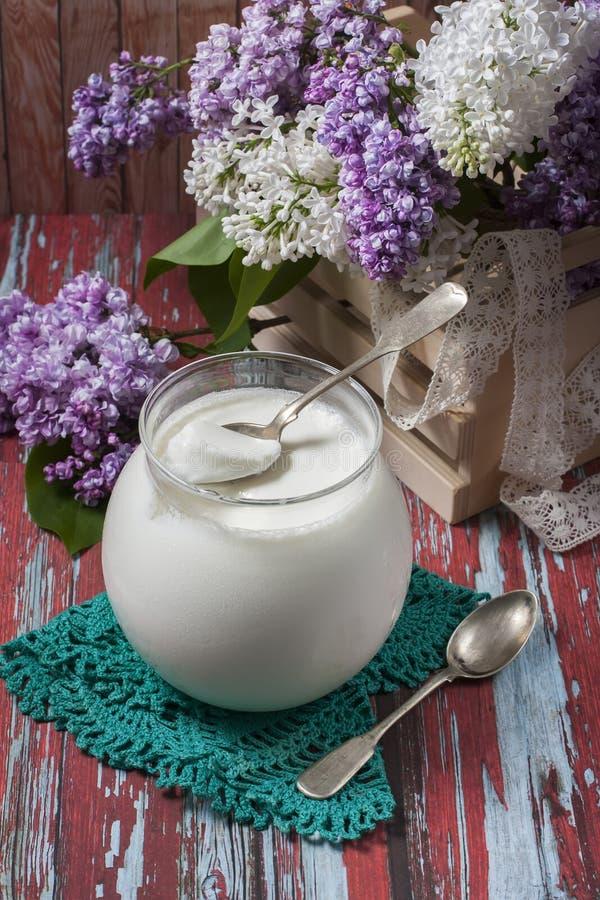 Domowej roboty jogurt w szklanym słoju, kwitnący bez kwitnie na drewnie zdjęcie stock