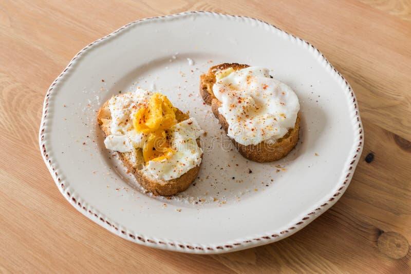 Domowej roboty Kłusujący jajka z pikantność i chlebem na Drewnianej powierzchni zazwyczaj słuzyć z kawą fotografia stock