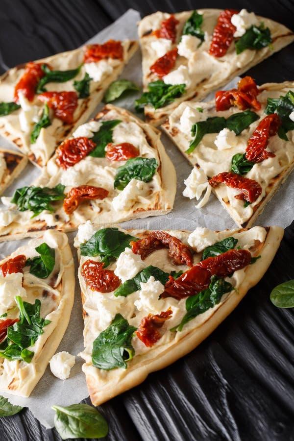 Domowej roboty kanapki z hummus, suszącymi pomidorami, szpinakami i koźlim serem w górę, pionowo obraz stock