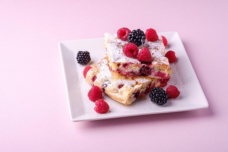 Domowej roboty kawałek tort, dwa pasztetowego plasterka z jagodami, malinowymi i jeżynowymi, sproszkowany cukier w białego kwadra zdjęcie royalty free