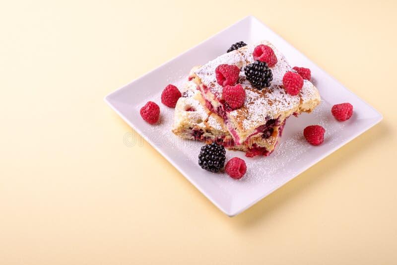 Domowej roboty kawałek tort, dwa pasztetowego plasterka z jagodami, malinowymi i jeżynowymi, sproszkowany cukier w białego kwadra fotografia stock
