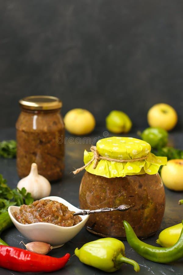 Domowej roboty kumberlandu adjika z gorącym pieprzem, czosnkiem, jabłkami, pietruszką i koperem w słoju, zdjęcie stock