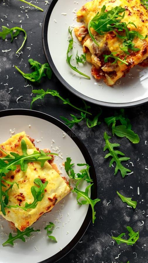 Domowej roboty lasagna z minced wołowiną Bolognese i bechamel kumberlandem nakrywał dzikiego arugula, parmesan ser zdjęcie stock