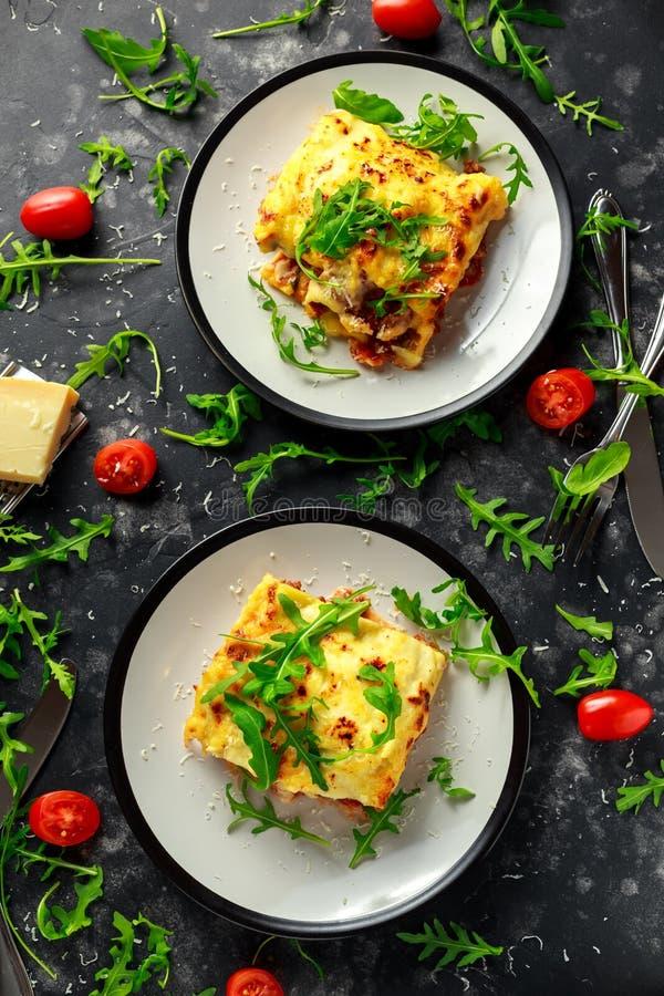 Domowej roboty lasagna z minced wołowiną Bolognese i bechamel kumberlandem nakrywał dzikiego arugula, parmesan ser fotografia royalty free