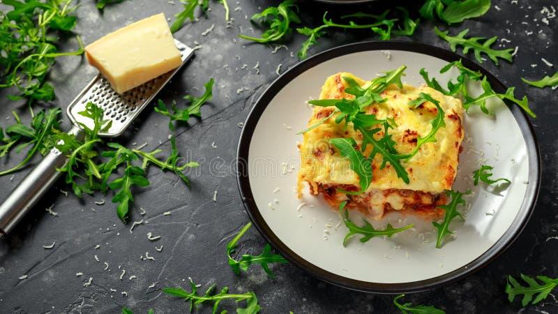 Domowej roboty lasagna z minced wołowiną Bolognese i bechamel kumberlandem nakrywał dzikiego arugula, parmesan ser obrazy royalty free