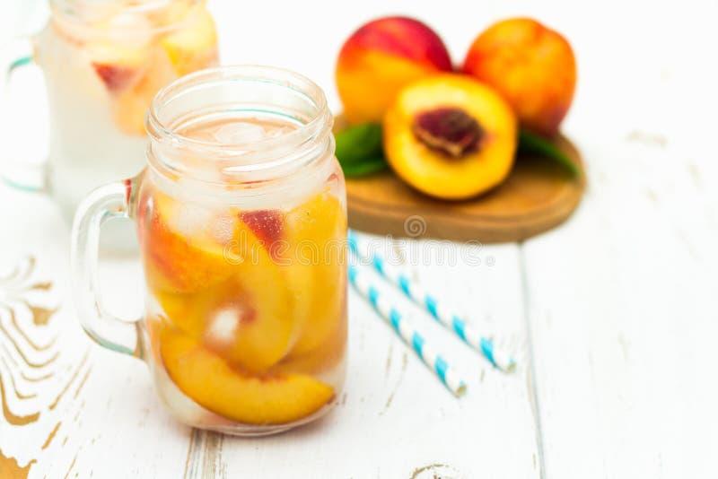 Domowej roboty lukrowa lemoniada z dojrzałymi brzoskwiniami Świeżej brzoskwini lodowa herbata w kamieniarza słoju obraz royalty free