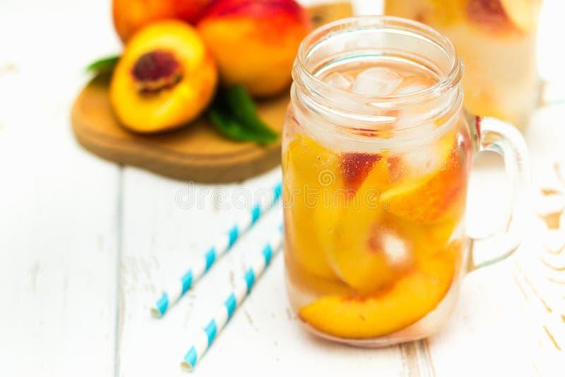 Domowej roboty lukrowa lemoniada z dojrzałymi brzoskwiniami Świeżej brzoskwini lodowa herbata w kamieniarza słoju fotografia royalty free