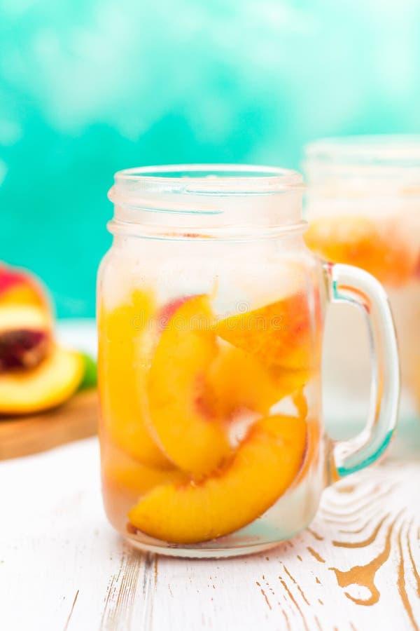 Domowej roboty lukrowa lemoniada z dojrzałymi brzoskwiniami Świeżej brzoskwini lodowa herbata w kamieniarza słoju fotografia stock