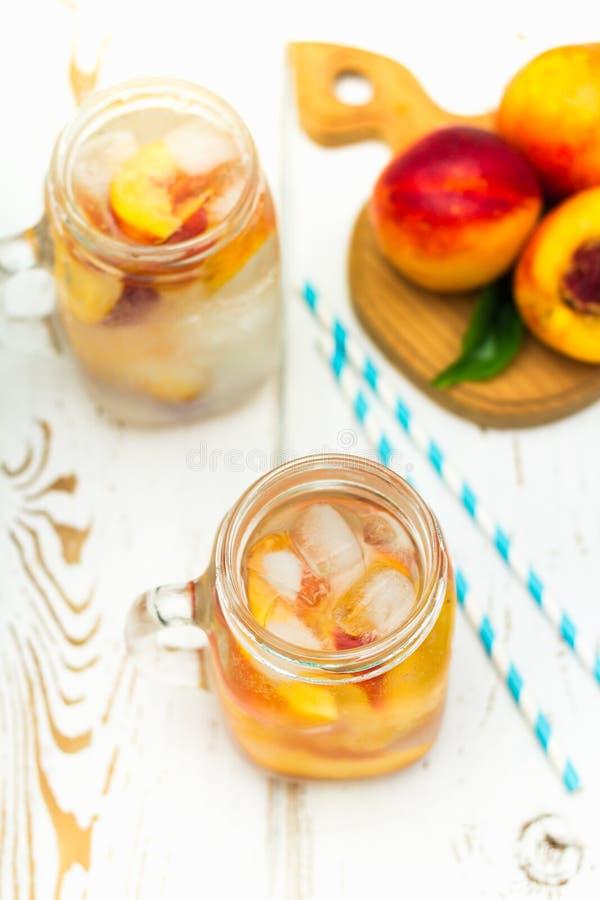 Domowej roboty lukrowa lemoniada z dojrzałymi brzoskwiniami Świeżej brzoskwini lodowa herbata w kamieniarza słoju Odgórny widok obrazy royalty free