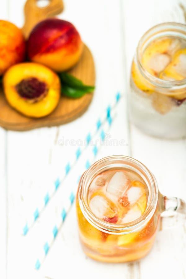 Domowej roboty lukrowa lemoniada z dojrzałymi brzoskwiniami Świeżej brzoskwini lodowa herbata w kamieniarza słoju Odgórny widok zdjęcie stock