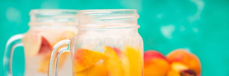 Domowej roboty lukrowa lemoniada z dojrzałymi brzoskwiniami Świeżej brzoskwini lodowa herbata w kamieniarza słoju sztandar zdjęcia royalty free