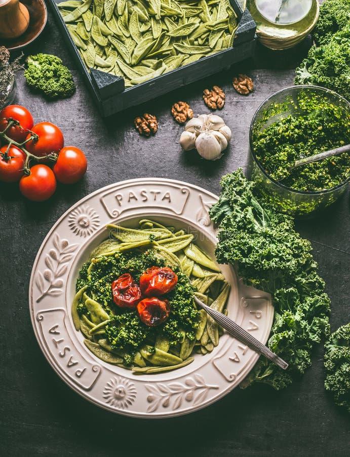 Domowej roboty makaron z surowym kale pesto i piec na grillu pomidorami w talerzu z rozwidleniem na kuchennym stole z składnikami obrazy royalty free