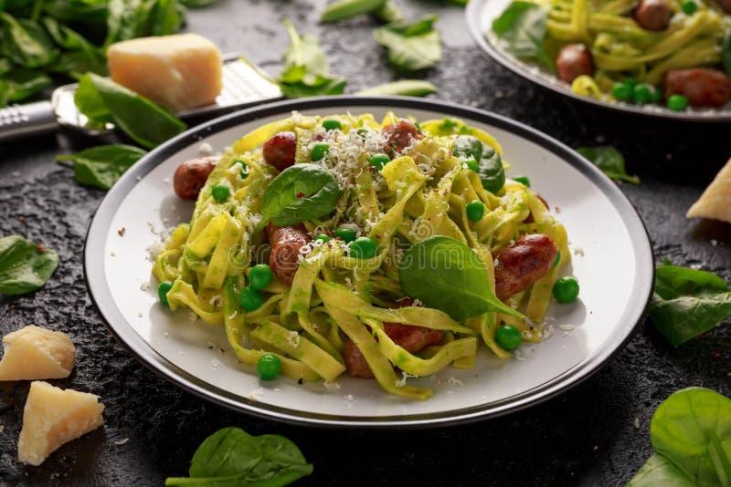 Domowej roboty makaron z zielonymi grochami, szpinaka pesto i kiełbasami, Parmezański ser zdrowa żywność fotografia royalty free