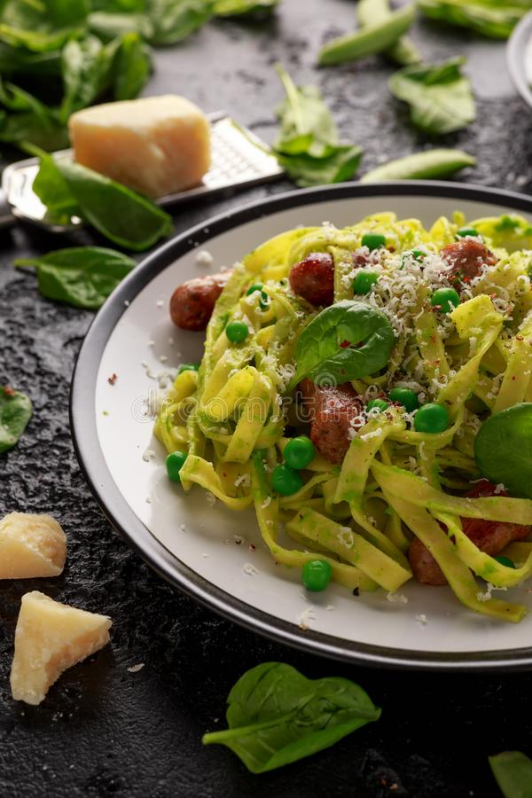 Domowej roboty makaron z zielonymi grochami, szpinaka pesto i kiełbasami, Parmezański ser zdrowa żywność fotografia stock
