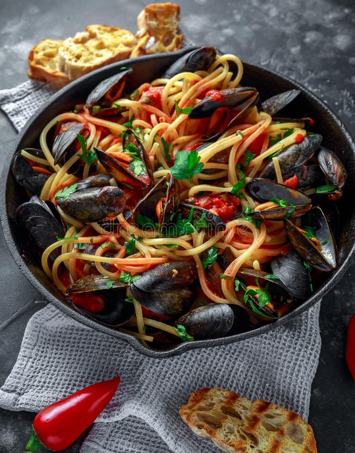 Domowej roboty makaronu spaghetti z mussels, pomidorowym kumberlandem, chili i pietruszką w nieociosanej rynience, niecka Dennego fotografia stock