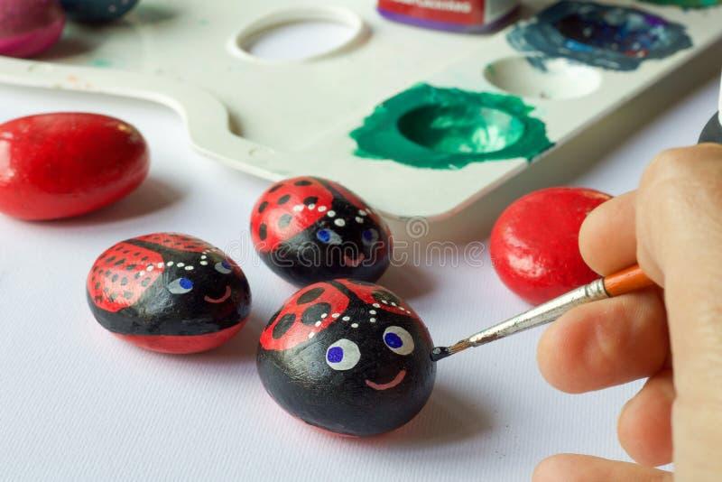 Domowej roboty malujący kamienie jako biedronki zdjęcie stock