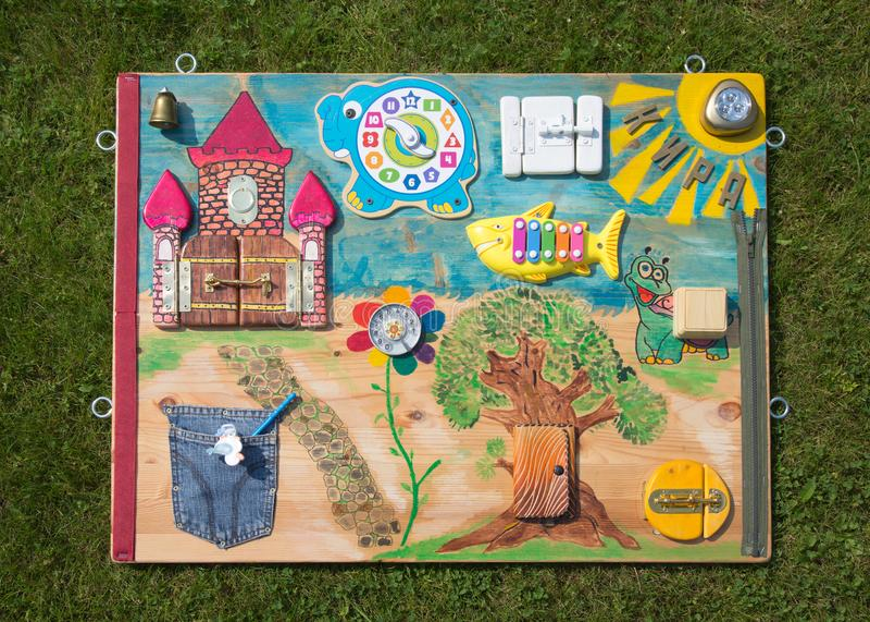 domowej roboty montessori dziecka zabawkarska deska rozdzielcza na w górę tło zieleni gazonu zdjęcie royalty free