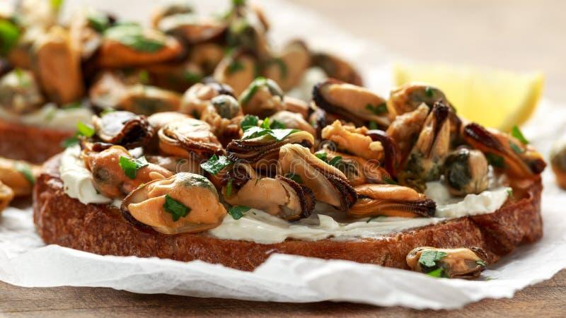 Domowej roboty Mussels na piec na grillu bruschetta, grzance z miękkim serem i ziele, zdjęcia royalty free