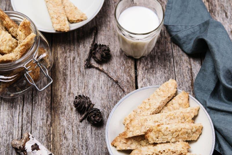 Domowej roboty oatmeal ciastka z szkłem mleko na popielatego rocznika drewnianym stole obrazy stock