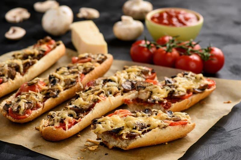 Domowej roboty piec na grillu baguettes z pieczarkami, pomidorami i serem, obrazy stock