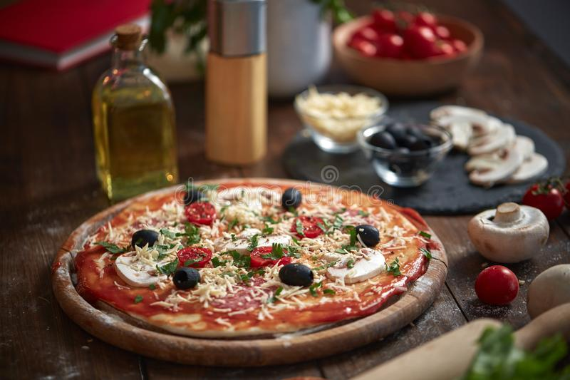 Domowej roboty pizza na drewnianej desce z pomidorami i salami, pieczarki, włoszczyzna styl na starym drewnianym stole zdjęcia royalty free