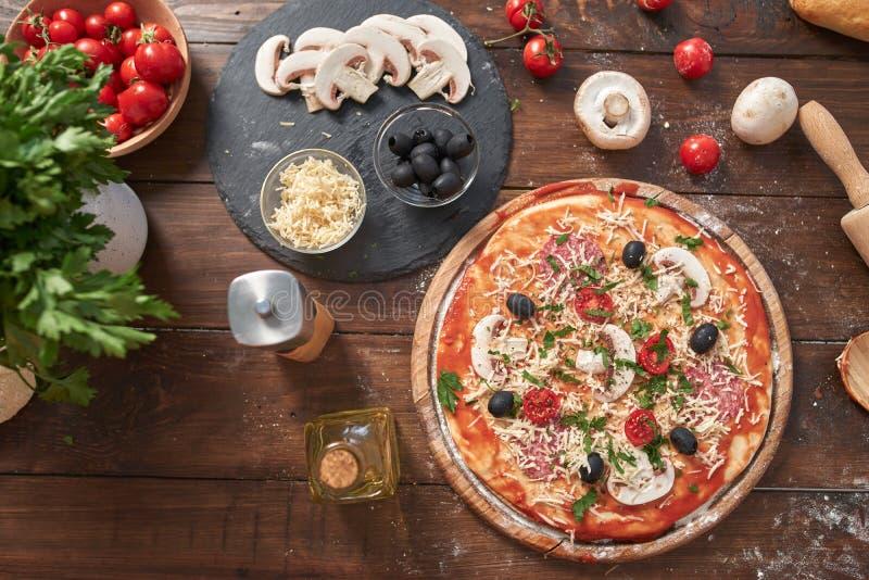Domowej roboty pizza na drewnianej desce z pomidorami i salami, pieczarki, włoszczyzna styl na starym drewnianym stole, odgórny w obraz stock