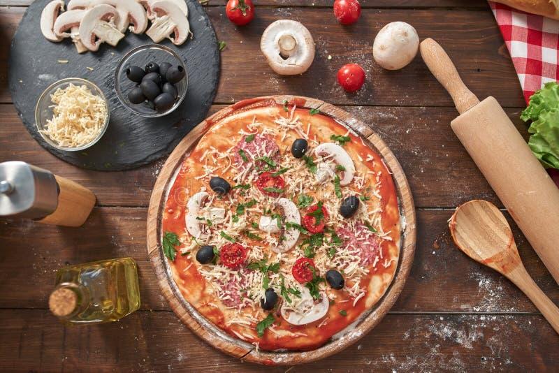 Domowej roboty pizza na drewnianej desce z pomidorami i salami, pieczarki, włoszczyzna styl na starym drewnianym stole, odgórny w obrazy royalty free