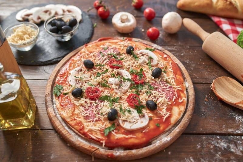 Domowej roboty pizza na drewnianej desce z pomidorami i salami, pieczarki, włoszczyzna styl na starym drewnianym stole, odgórny w zdjęcie royalty free