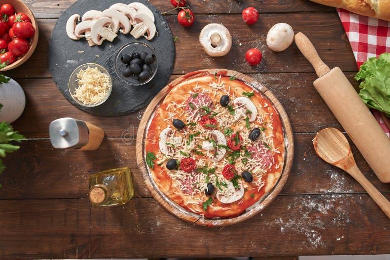 Domowej roboty pizza na drewnianej desce z pomidorami i salami, pieczarki, włoszczyzna styl na starym drewnianym stole, odgórny w fotografia stock
