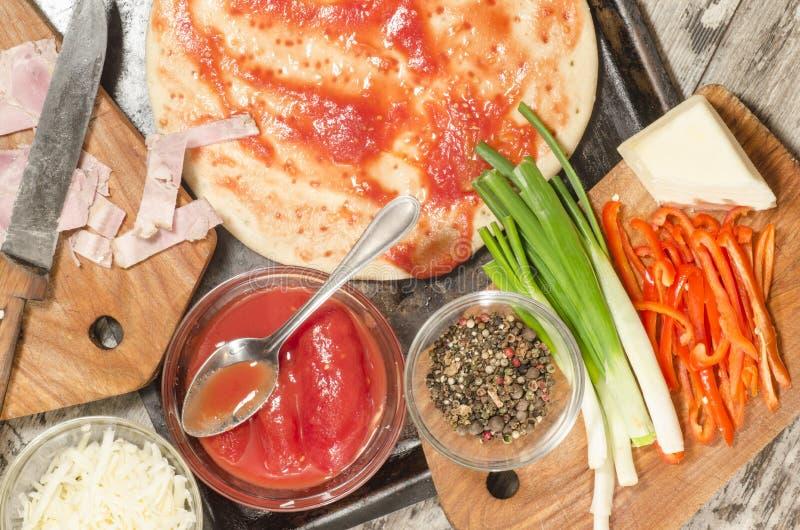 Domowej roboty pizza na wypiekowej tacy i składnikach dla gotować obraz royalty free