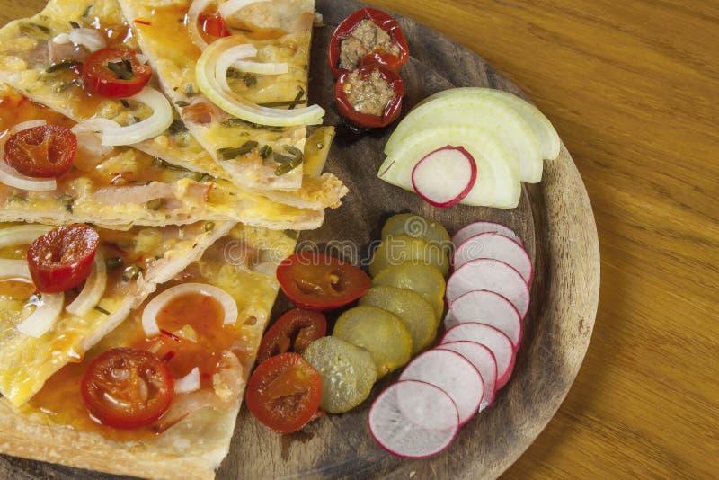 Domowej roboty pizza, pokrajać na ciapania drewnianych deskach, doprawiać z chili pieprzami zdjęcie royalty free