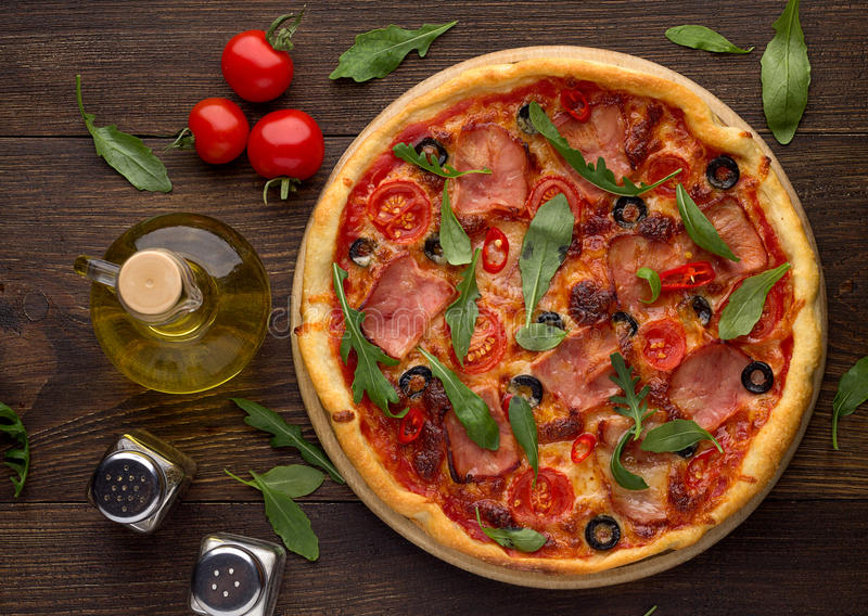 Domowej roboty pizza z baleronem, pomidorami, oliwkami i arugula na ciemnym drewnianym stole, zdjęcia stock