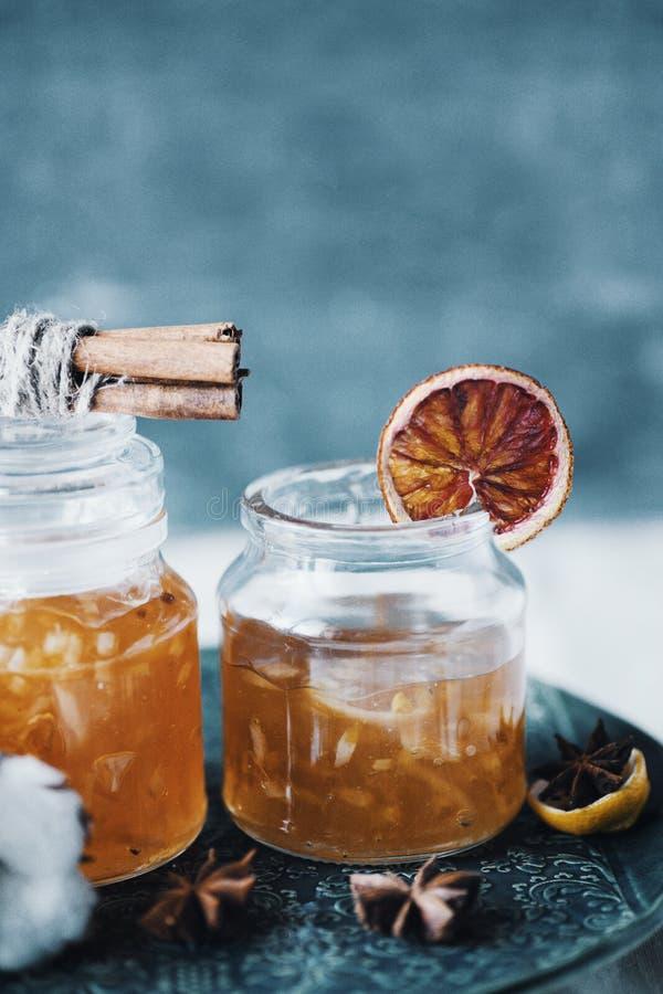 Domowej roboty pomarańczowy dżem w szklanym słoju na błękicie lub popielatym tle obraz stock