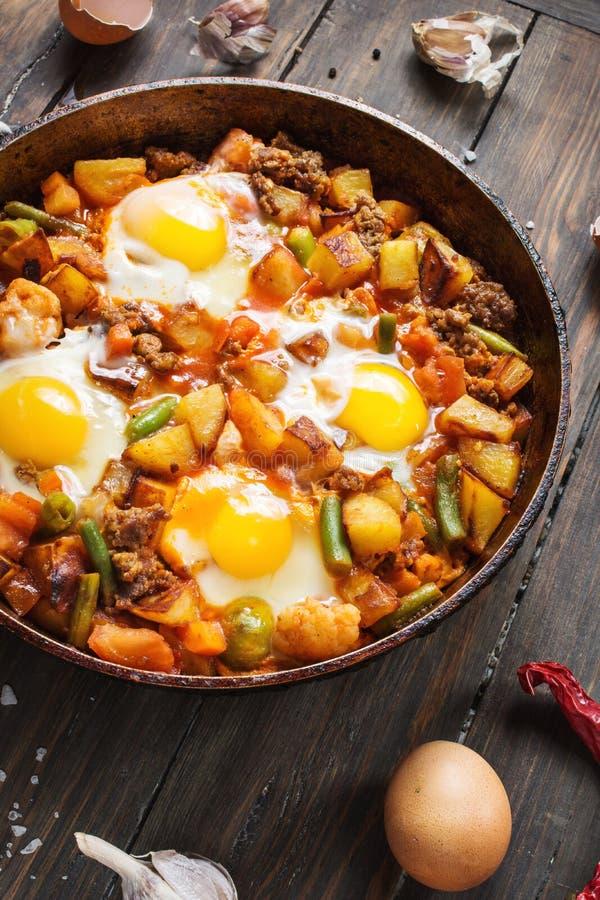 Domowej roboty Serdecznie Śniadaniowa rynienka z jajko grulami i minced mięsem na drewnianym stole zdjęcie stock