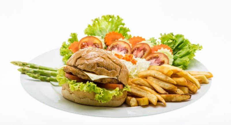 Domowej roboty serowy kurczaka hamburger z świeżą sałatką na talerzu fotografia stock